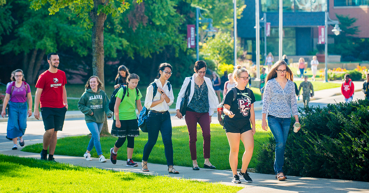Students and staff walk across campus