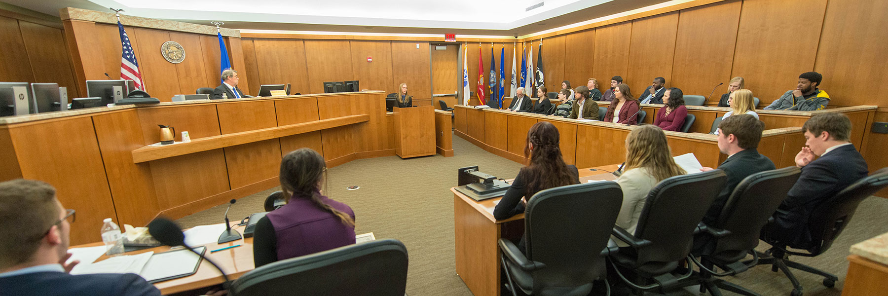 Legal studies students carry out a mock trial in a courtroom.
