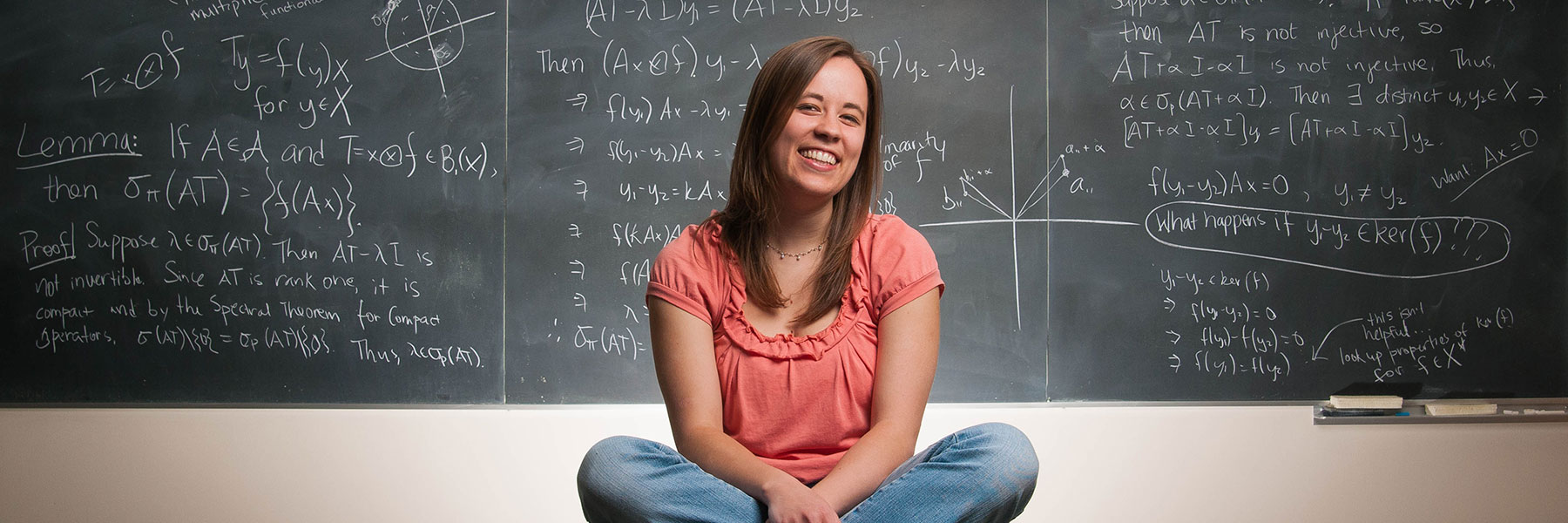 Mathematics student Tova Brown in front of a chalkboard displaying equations.