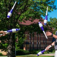 Students on campus green practice their juggling skills