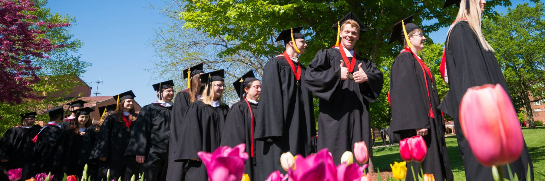 Graduates process across the campus before the commencement ceremony