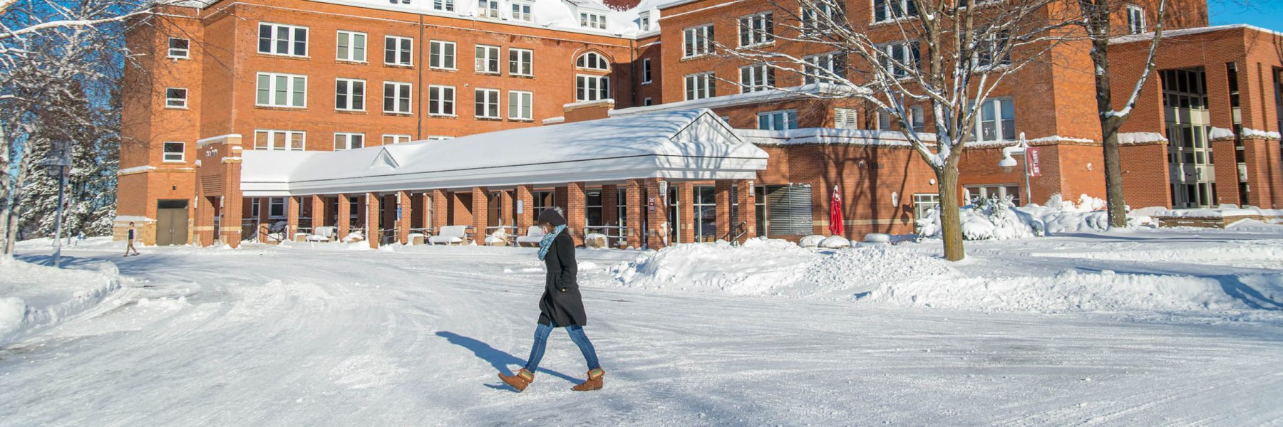Female student walks by Old Main in winter