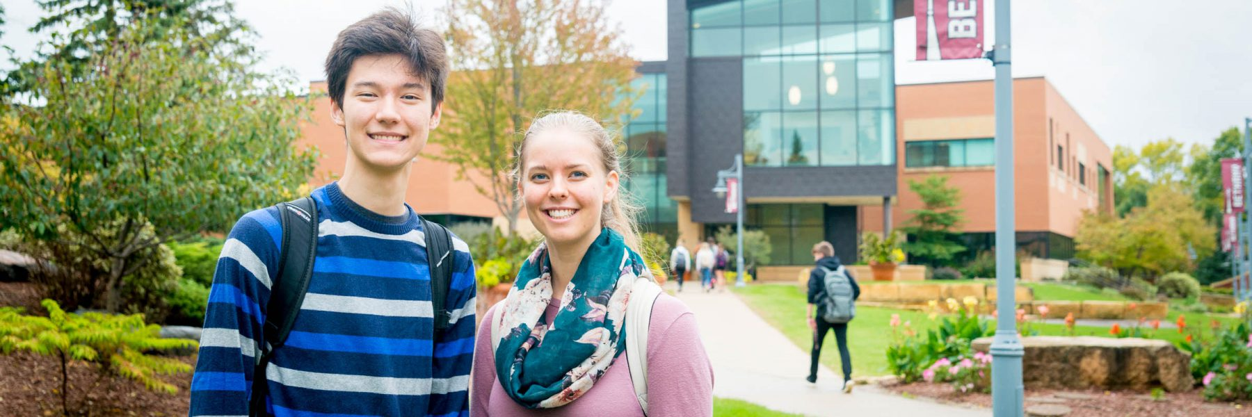 Two students pose for photo in front of Honsey Hall