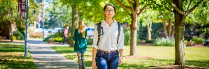 Female students walking outside under trees