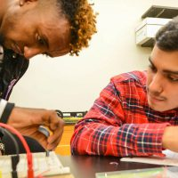 Students during physics class assemble and test a circuit board