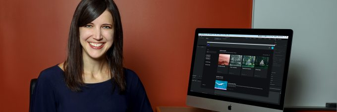 Photo of Professor Amanda Quist next to iMac with design software open