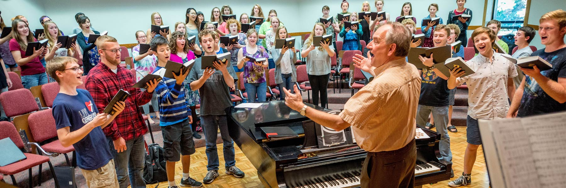 Prof. Dennis Marzolf directs a Bethany Concert Choir practice as they sing a hymn in Bethany's Silber Hall.