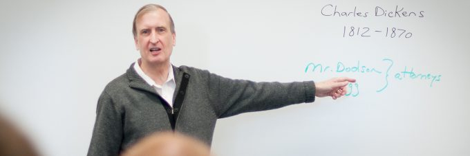 Dr. Robert Hanna instructs students at a white board about Charles Dickens.