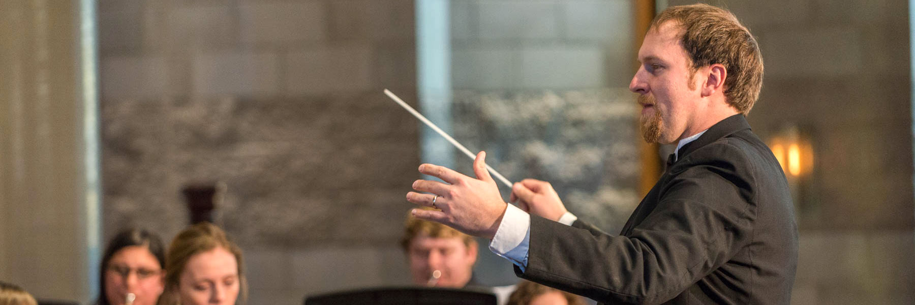 Benjamin Faugstad directs the Concert Band during a performance in Trinity Chapel at Bethany Lutheran College.