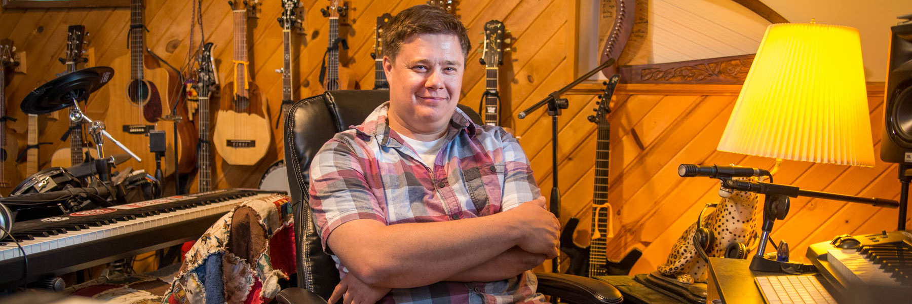 Professor Benji Inniger of the BLC Theater Department sits in his recording studio surrounded by musical instruments.