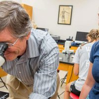 Prof. Doyle Holbird looks into a microscope in the Bethany biology lab.