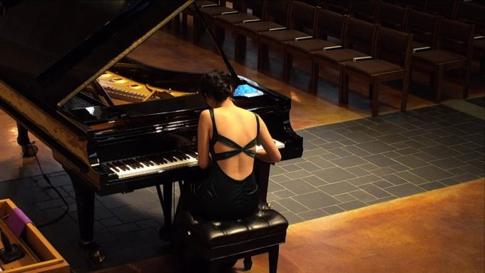 Student Sarah Wei plays a grand piano in Trinity Chapel during her Junior Piano Recital.