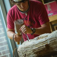 Working in the art studio, Christiansen uses a mallet and chisel to sculpt a large block of wood.