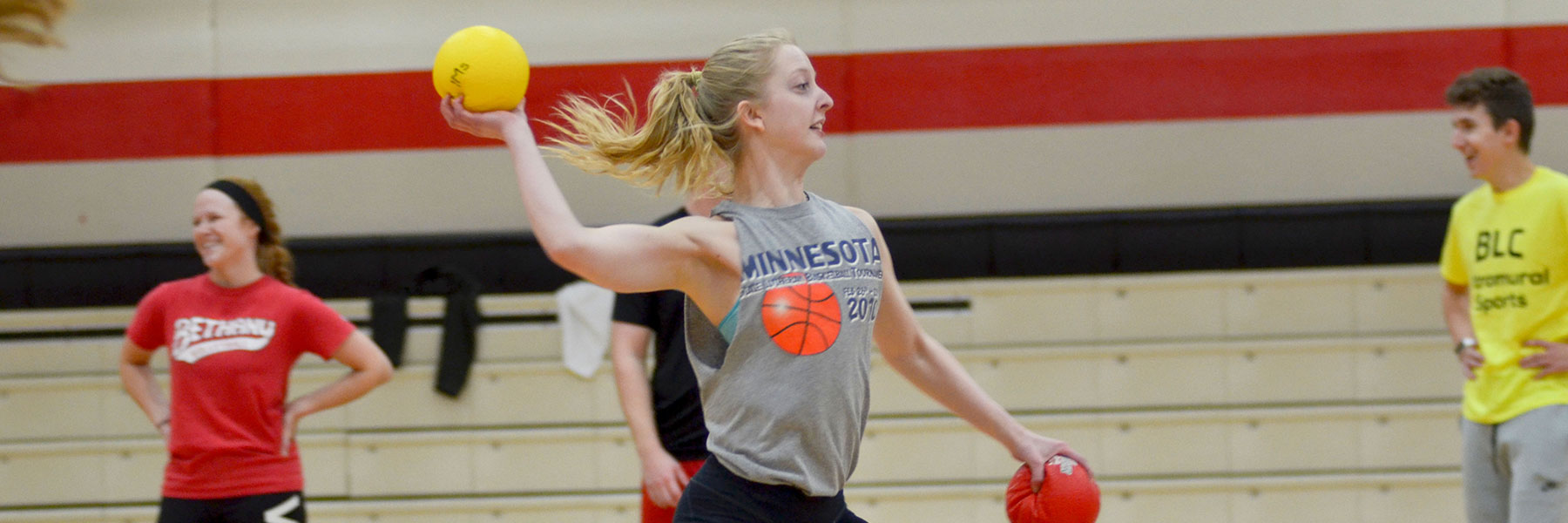 A student in the gymnasium throws balls during an intramural game as other students look on.