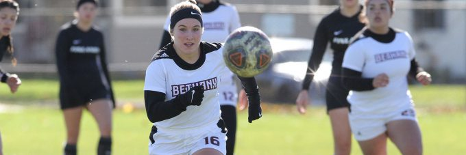 A Bethany Viking Women's Soccer player drives a ball forward with other players in pursuit.