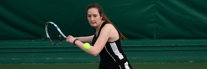 A tennis player prepares to hit an incoming ball.