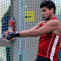 A student participates in a hammer throw during a track and field meet.