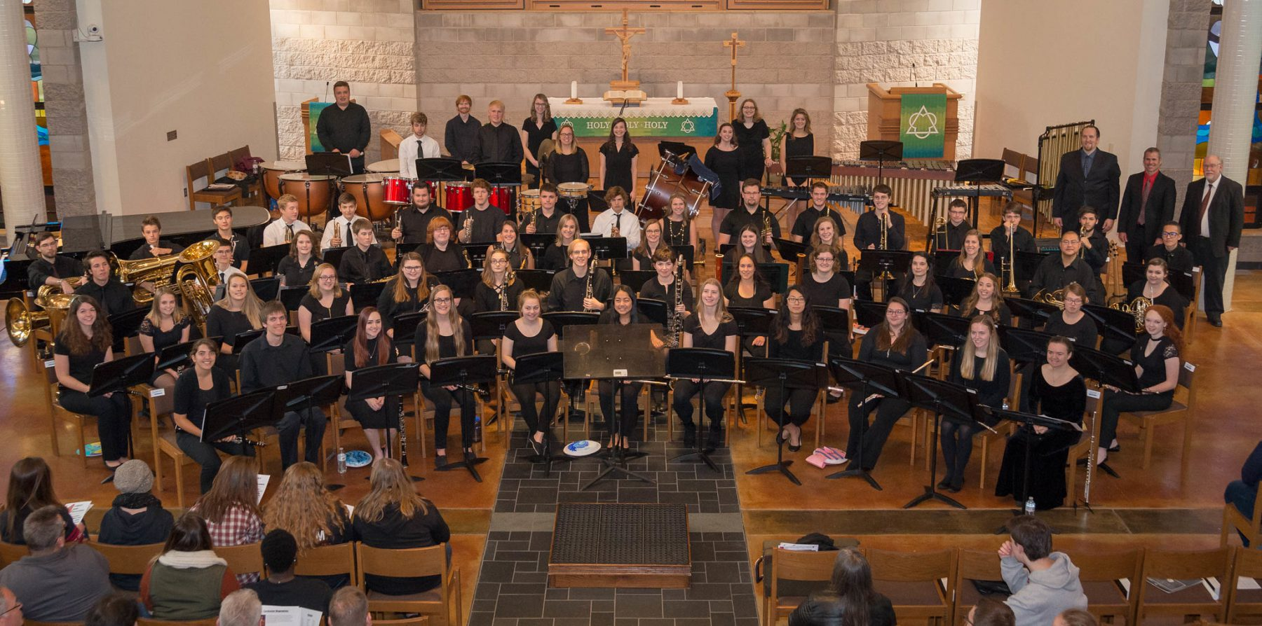 Group photo of performers with their instruments at the 2018-10 Concert Band Invitational, seated at the front of the chapel