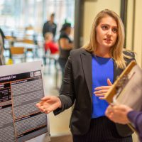 A student speaks with an attendee about her psychology research poster