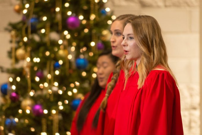 Closeup of three women of the choir singing at the Christmas at Bethany concert in December 2018, with a Christmas tree in the background