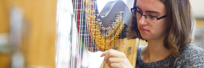 Female student tuning a harp