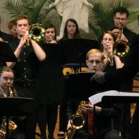 students play instruments as part of a jazz music ensemble while one of them sings