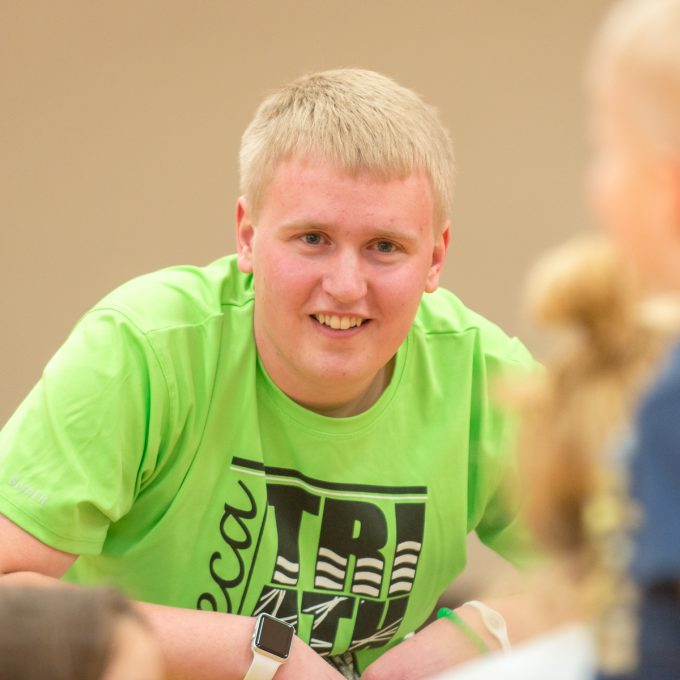 Education major Noah Battenfeld in gym with young students.