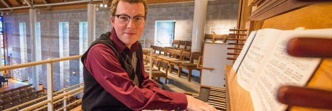 student sitting at pipe organ with fingers on keys
