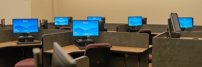 computer monitors set out on desks in a lab