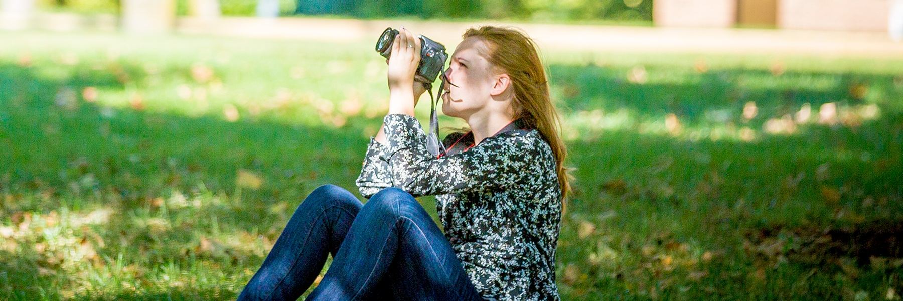 Student sitting on ground outside on a sunny day photographing into the trees.