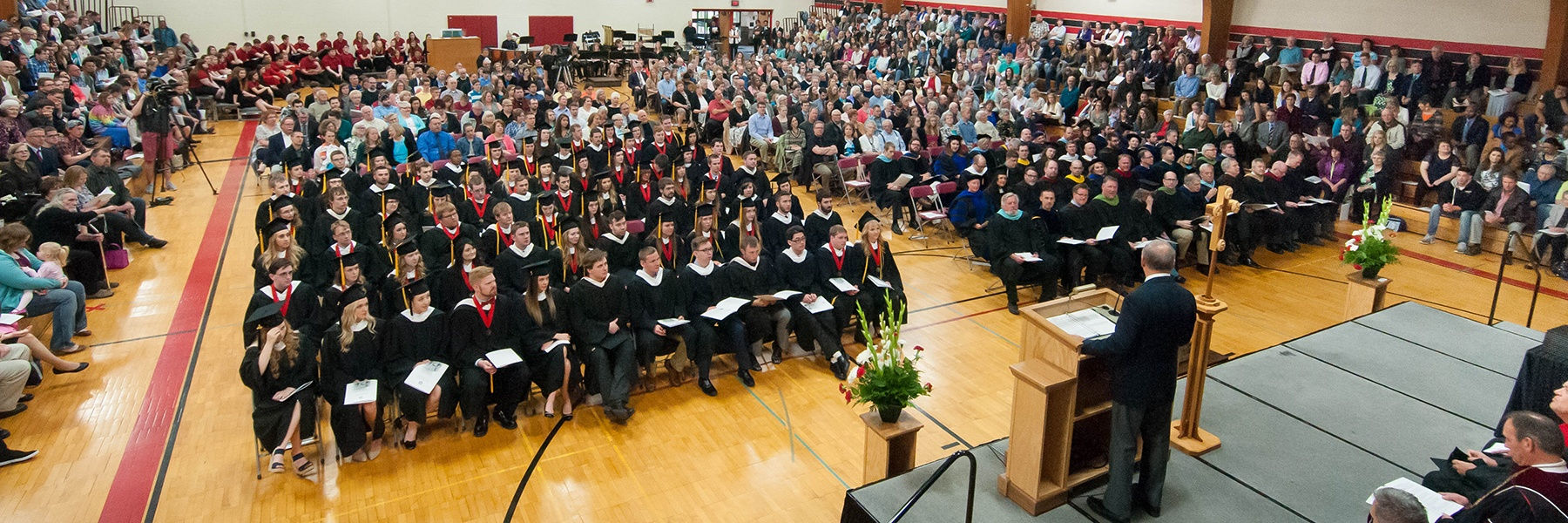 People seated in the Ronald J. Younge gymnasium for a commencement ceremony listening to the guest speaker at a podium.