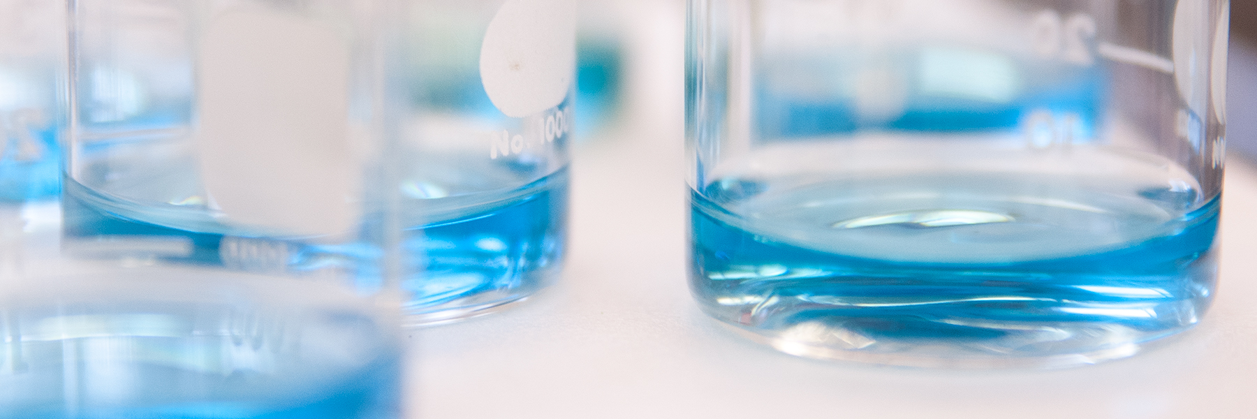 Chemistry beakers filled with blue liquid