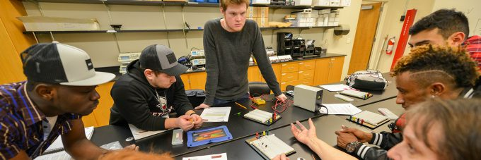 students gathered around table in electronics lab