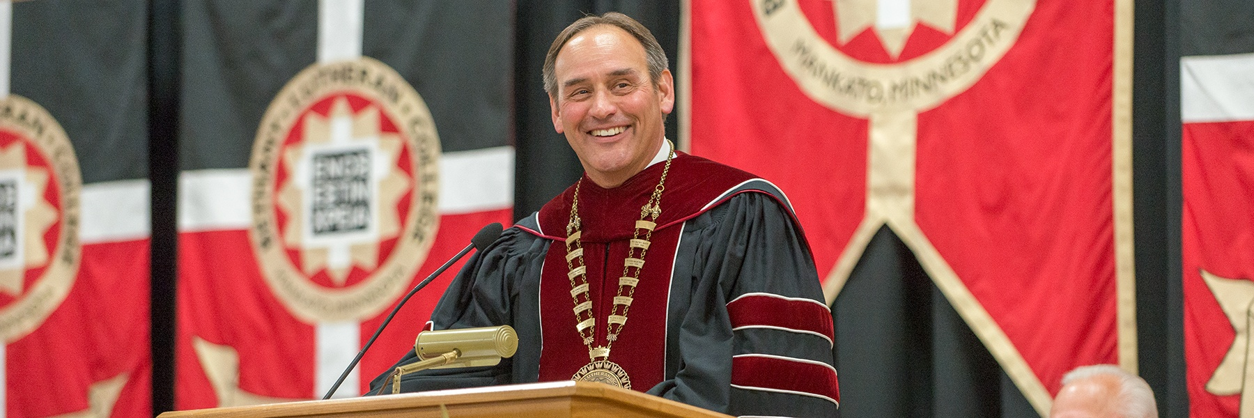 President Gene Pfeifer smiles at a podiium during the 2019 commencement ceremony.