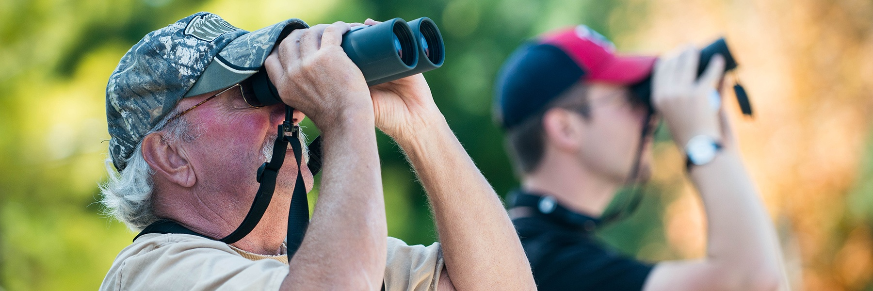 Two birdwatchers use binoculars to view and count hawks as part of Bethany's Hawkwatch