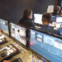 students work on computers and monitor activity on video screens during a tv broadcast