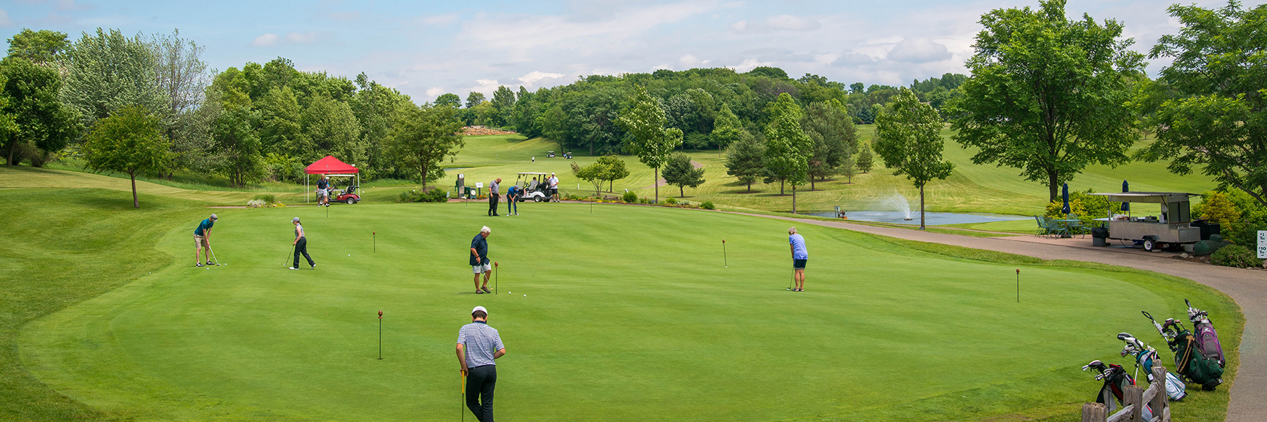 golfers practice putting on a putting green before a tournament
