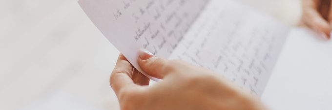 hand written letter held by womans hands