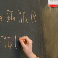 Student at chalk board writing out mathematic formulas.
