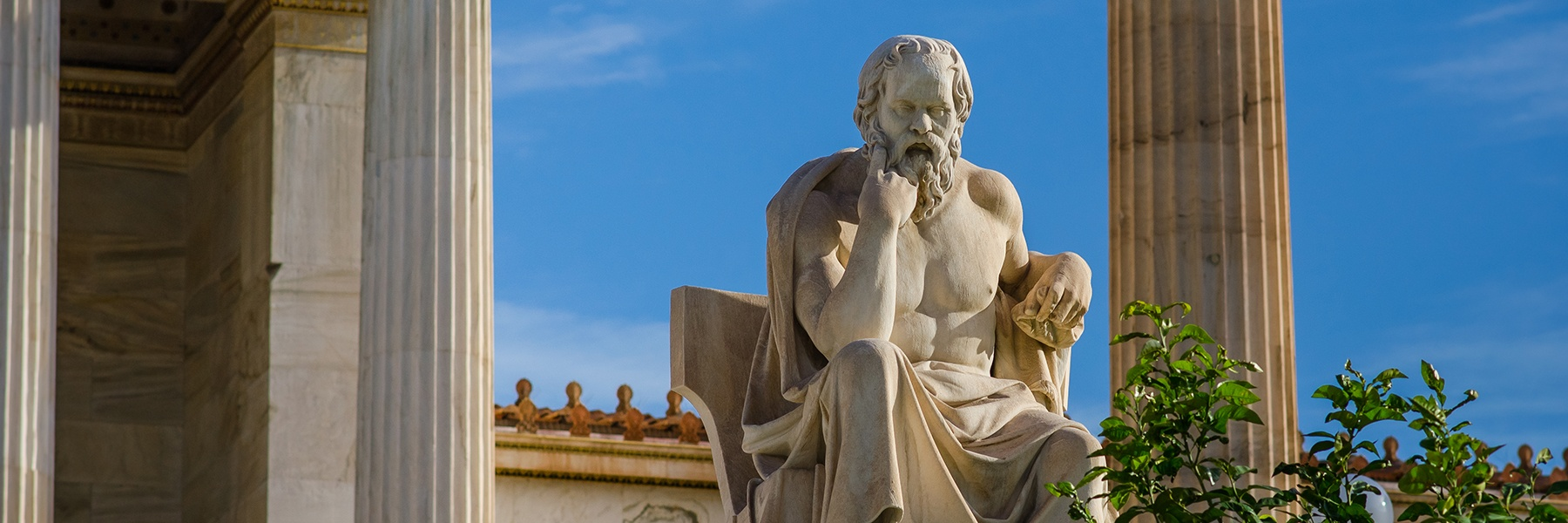 Image of ancient statue of the great Greek philosopher Socrates on background of classical columns.