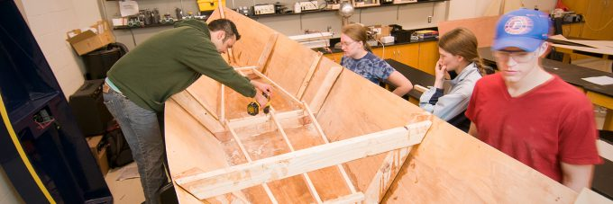 Students assemble a boat made of wood for a physics class lab