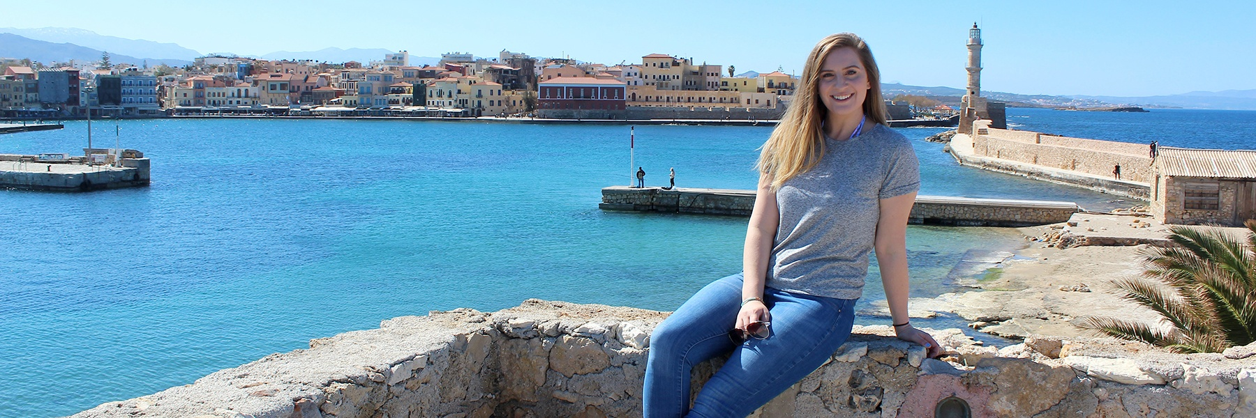 female student sitting on a wall in front of a body of water overseas