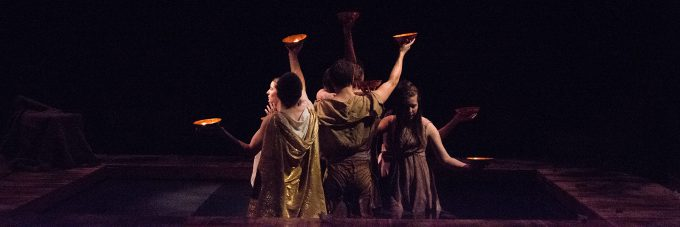 Theatre actors holding bowls with candles lighting up a dark room on stage