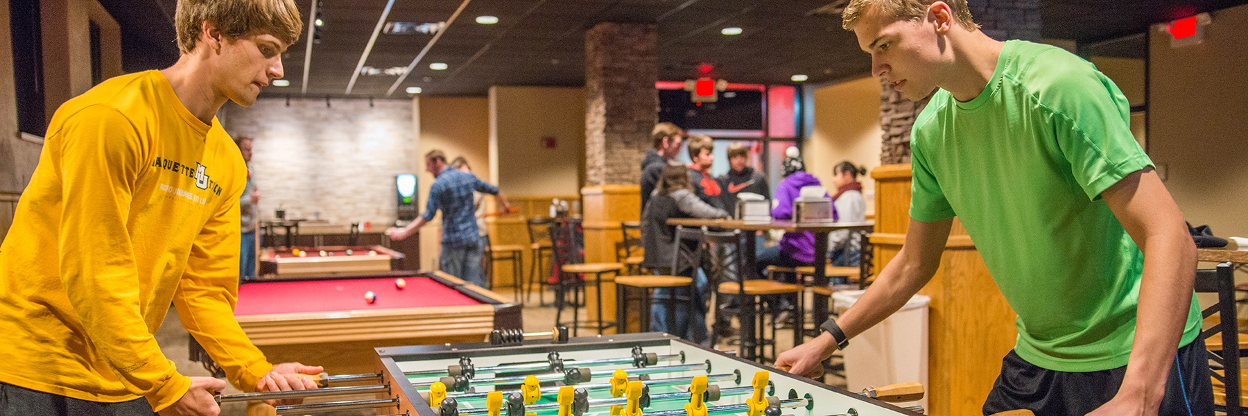 students play a game of foosball in a room with a pool table and others mingling