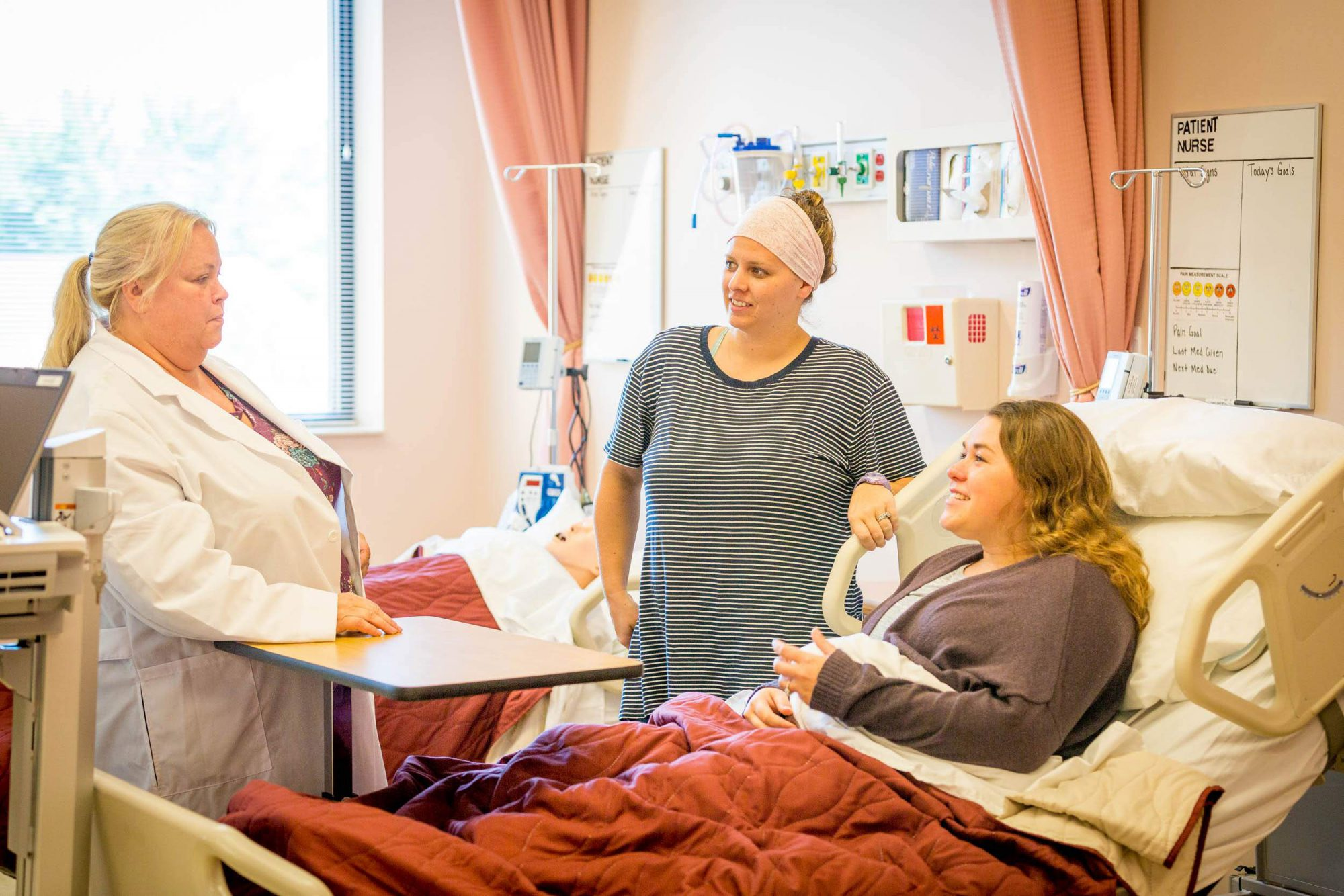 Nursing students practice their bedside patient skills under supervision of a professor in the nursing lab