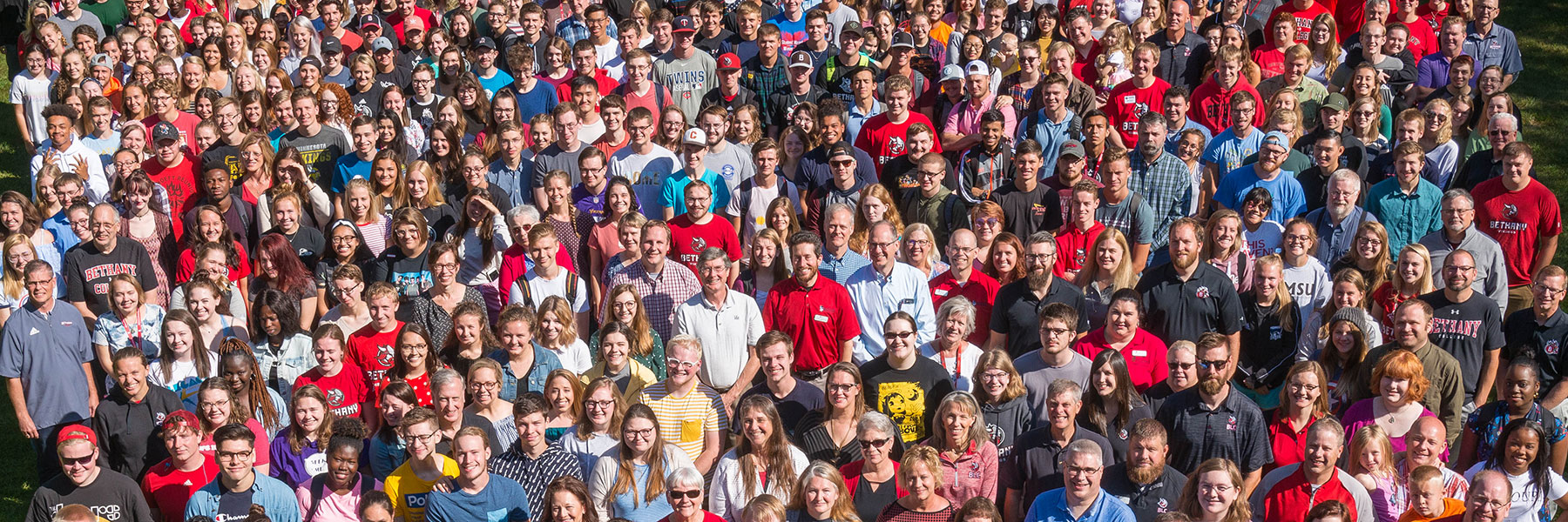 large crowd of people together looking right at camera on a sunny day