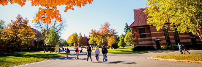 Picture of campus in the fall, students walking on road