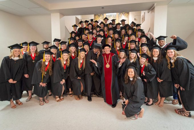 BLC President Dr. Gene Pfeifer stands with the Spring 2018 graduating class on the stairs in Old Main just before the commencement ceremony begins.