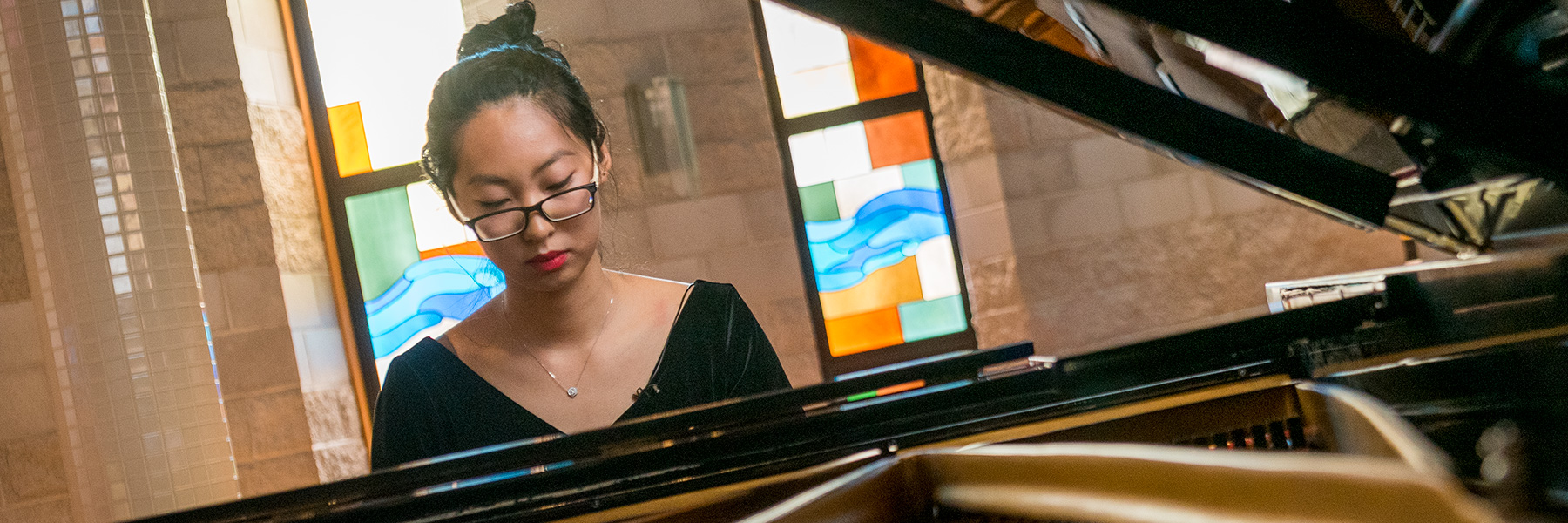 Sarah Wei behind the piano in Trinity Chapel