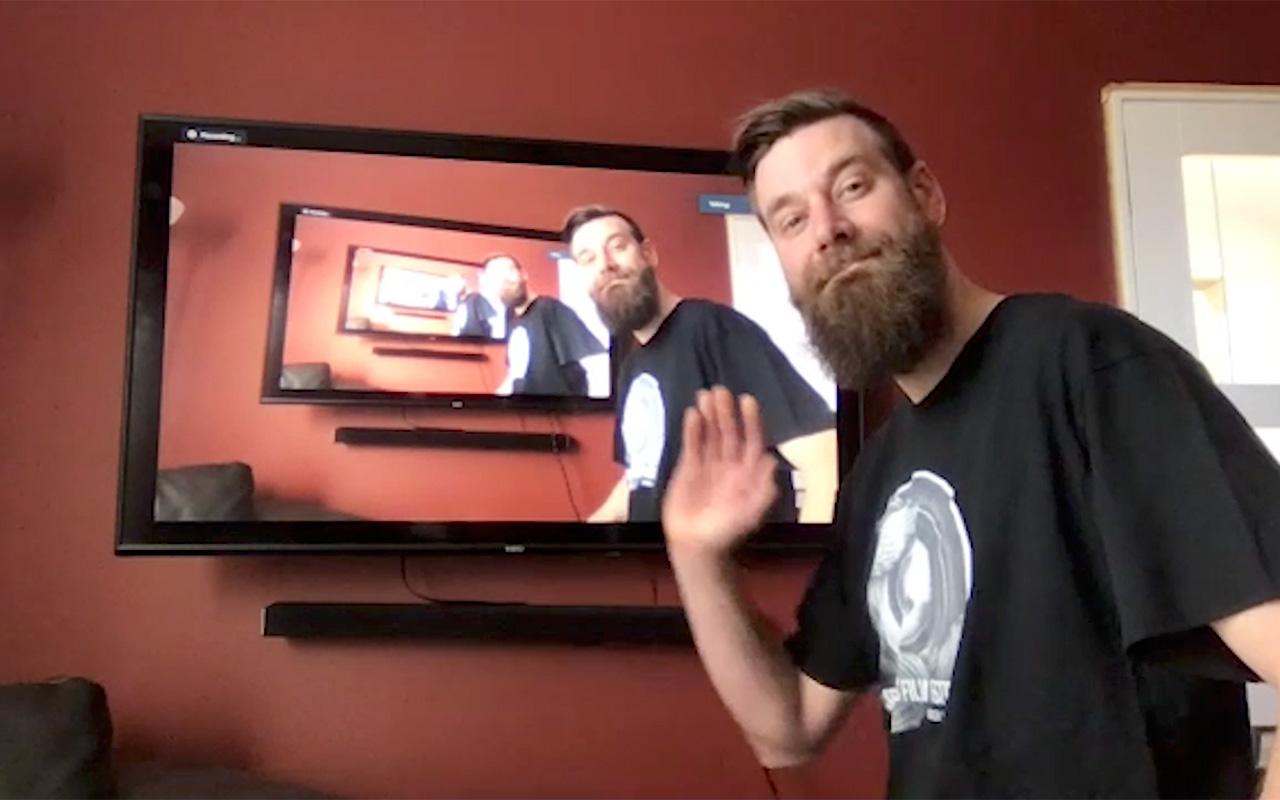 Professor Kurt Paulsen stands by an image of himself on a screen